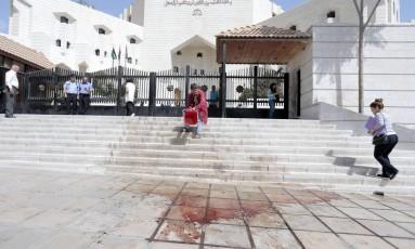 Homem limpa o sangue na calçada em frente ao tribunal onde o jordaniano Nahed Hattar respondia a acusações de divulgar charge ofensiva ao Islã: escritor, cristão, foi morto por atirador não identificado Foto: AFP/AHMAD ALAMEEN