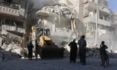 Civis assistem enquanto um trator limpa os destroços de prédio atingido pelos bombardeios do regime sírio em Aleppo: possíveis crimes de guerra Foto: THAER MOHAMMED / AFP/THAER MOHAMMED