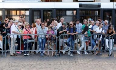 Grupo de pessoas espera na frente do Palácio de Chigi, sede do governo da Itália, durante uma reunião do gabinete italiano em Roma Foto: ALESSANDRO BIANCHI / REUTERS