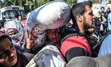 Refugiados sírios caminham de volta a cidade de Jarabulus na fronteira com a Turquia Foto: BULENT KILIC / AFP