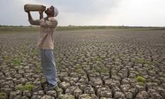 Trabalhador rural bebe água no leito seco de uma represa no estado de Maharashtra, região da Índia assolada por calor e estiagem Foto: Manish Swarup / AP
