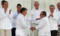 O presidente da Colômbia Juan Manuel Santos (esquerda) e o comandante das Forças Armadas Revolucionárias da Colômbia (Farc) Rodrigo Londono (conhecido como Timochenko) apertam as mãos após assinarem acordo de paz Foto: Fernando Vergara / AP