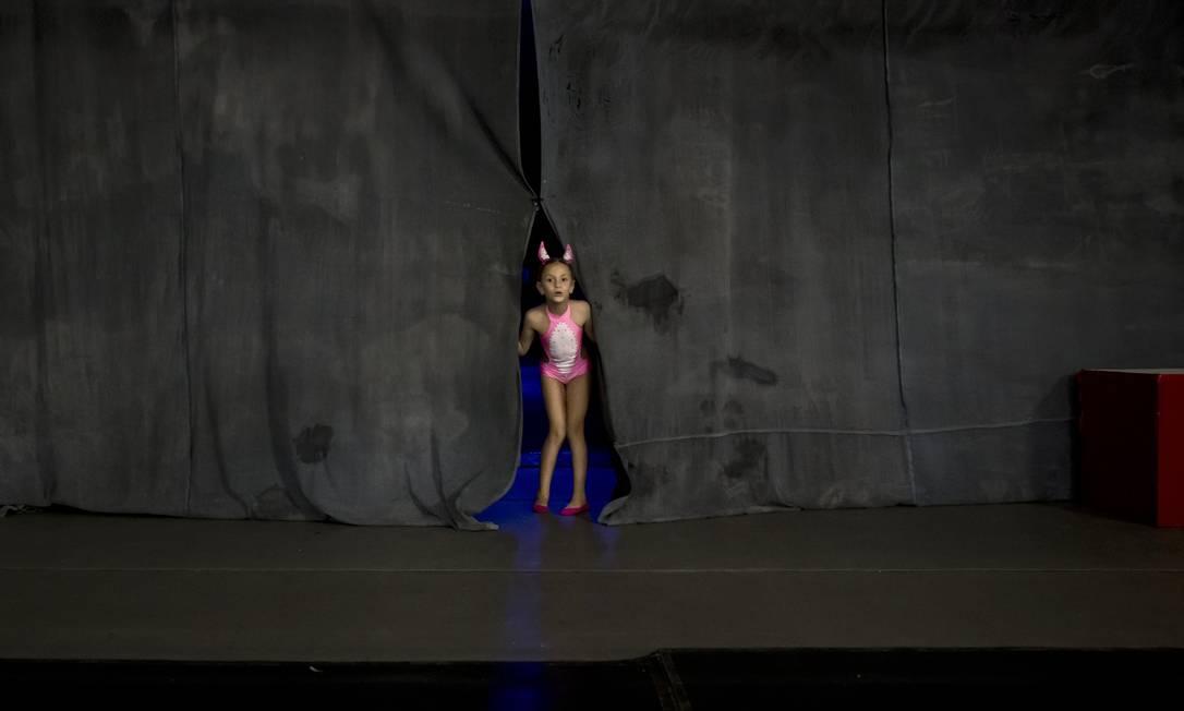 Diana Romaniuc, 7 anos, entre as cortinas antes de competir na categoria de filhos do Miss Pole Dance Contest Romênia Vadim Ghrida / AP
