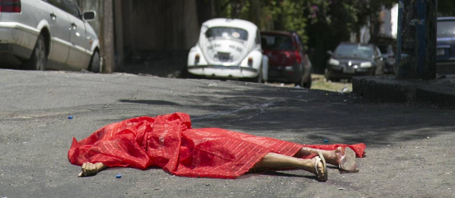 """Corpo de uma pessoa morta a tiros no final do desfile do bloco Céu na Terra no carnaval deste ano no Rio: mesmo com toda aparente violência, taxa de homicídios nas sociedades modernas é muito inferior à que seria """"natural"""" de nossa espécie Foto: Leo Martins"""