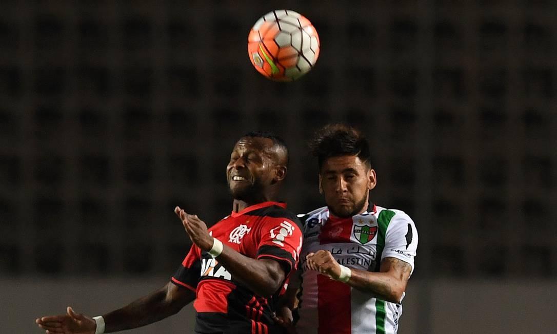 Chiquinho, do Flamengo, disputa a bola no alto com Torres, do Palestino VANDERLEI ALMEIDA / AFP