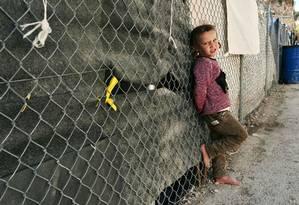 Menina posa para foto em campo de refugiados da ilha de Chios, na Grécia Foto: LOUISA GOULIAMAKI / AFP