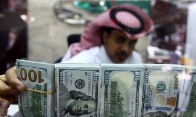 Funcionário saudita faz troca de notas de dólares: país ameaça tirar investimentos dos EUA Foto: FAISAL AL NASSER / REUTERS