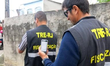 Fiscais do TRE seguem o sinal do wi-fi em Vila Serrana, localidade de Magé, oferecido por candidato a vereador Foto: Vera Araújo