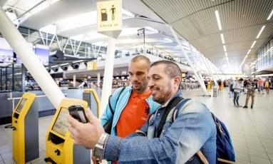 Fã posa ao lado do jogador Wesley Sneyder e aproveita o wi-fi grátis do aeroporto de Schiphol, em Amsterdã Foto: AFP / Robin van Lonkhuijsen