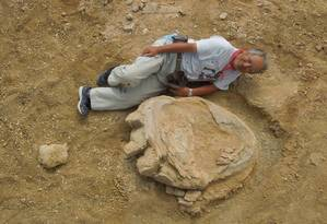 This handout picture taken on August 21, 2016 and released by Okayama University of Science and Mongolian academy of sciences joint expedition on September 30 shows Okayama University of Science Professor Shinobu Ishigaki lying next to a dinosaur footprint in Gobi Desert. A Mongolia-Japan joint expedition has found four fossil footprints in a layer of earth that dates back 70-90 million years ago in Gobi Desert. / AFP PHOTO / Okayama University of Science an / HO Foto: HO / AFP