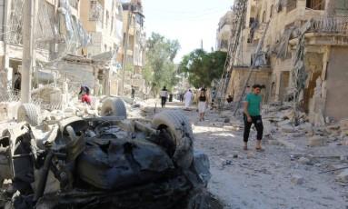 Moradores passam por carro destruído e escombros em Seif al-Dawla, em Aleppo Foto: ABDALRHMAN ISMAIL / REUTERS