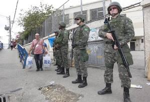 Militares fazem segurança em frente à zona eleitoral na Maré, durante as eleições de 2014 Foto: Márcio Alves / Agência O Globo/4-10-2014
