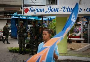 Apoio na Baixada: cabo eleitoral passa diante de militares a postos na praça central de Cabuçu, em Nova Iguaçu Foto: Pablo Jacob / Pablo Jacob