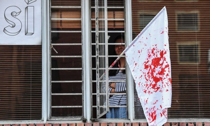 Partidária do acordo de paz, uma mulher coloca em sua janela uma bandeira suja de vermelho, como se fosse sangue, depois de conhecer o resultado do referendo Foto: LUIS ACOSTA / AFP