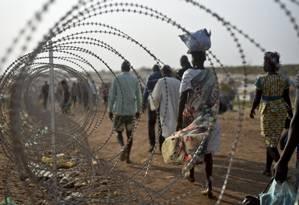 Deslocados caminham perto de cerca de arame farpado no Sudão do Sul, países que vive uma das mais difíceis situações de direitos humanos no mundo Foto: Jason Patinkin / AP