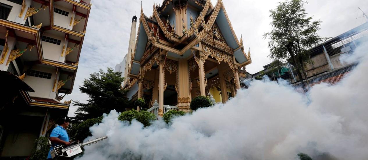 Agente de saúde espalha inseticida contra mosquitos em templo de Bangcoc Foto: Chaiwat Subprasom / Reuters