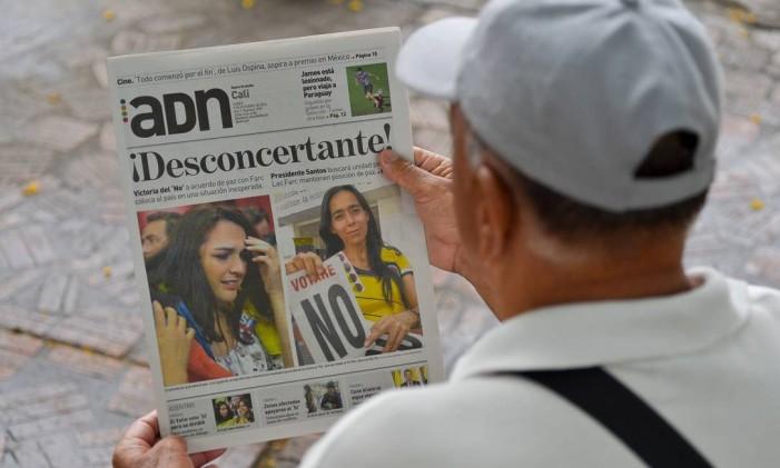 """Em Cali, um homem lê um jornal anunciando os resultados do referendo que, surpreendentemente, disse """"não"""" ao acordo de paz entre o governo colombiano e os guerrilheiros das Farc Foto: LUIS ROBAYO / AFP"""