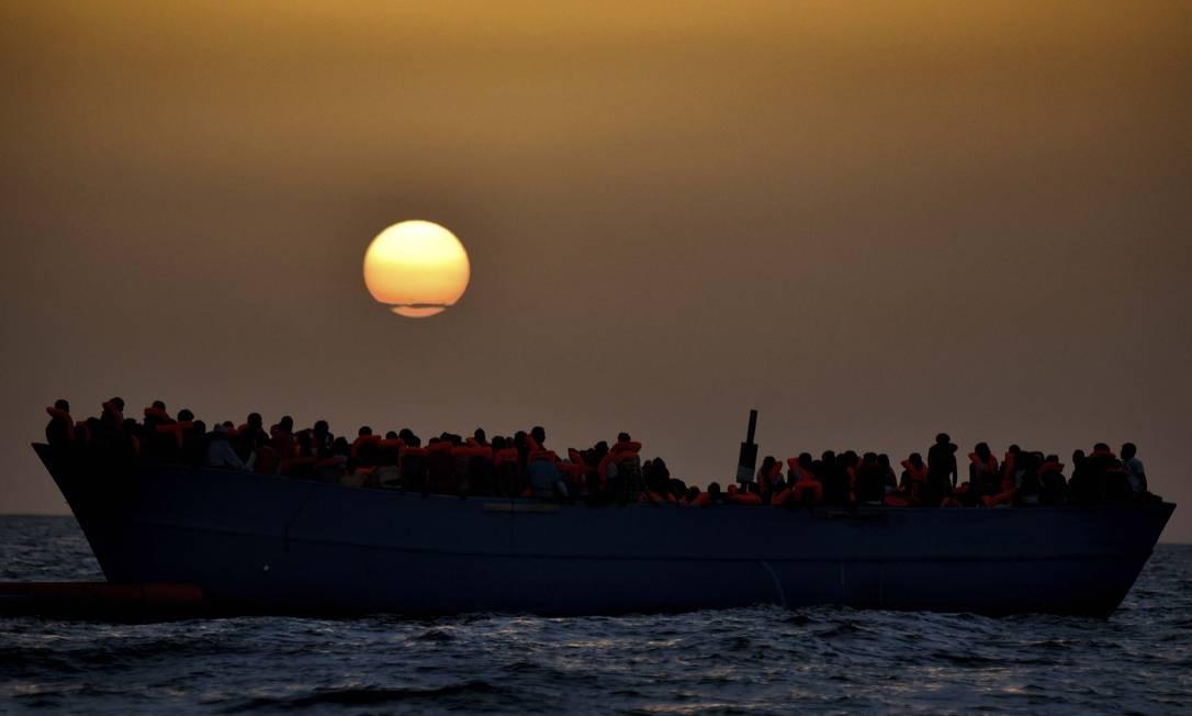Grupo de imigrantes aguarda resgate no Mar Mediterrâneo, a 20 milhas náuticas da costa da Líbia, enquanto o sol se põe. Segundo relatório da Organização Internacional para as Migrações (OIM), 426 pessoas morreram no mar este ano tentando chegar à Europa Foto: ARIS MESSINIS / AFP