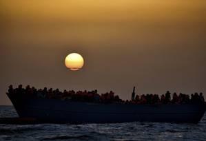 Imigrantes aguardam resgate enquanto o sol baixa no Mar Mediterrâneo, a 20 milhas náuticas da costa da Líbia Foto: ARIS MESSINIS / AFP