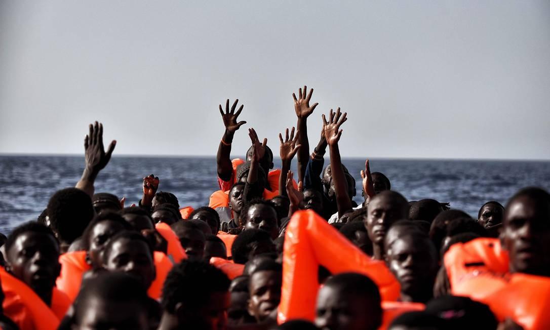 Imigrantes pedem socorro durante travessia no Mar Mediterrâneo, em outubro de 2016 Foto: ARIS MESSINIS / AFP