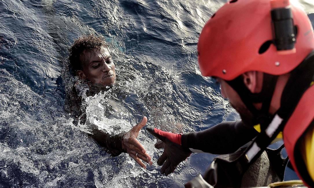 Membro da ONG Proactiva ajuda a resgatar uma pessoa na costa norte da Líbia, em 3 de outubro de 2016. Cerca de 3.750 imigrantes resgatados foram transferidas a centros de detenção na Líbia Foto: ARIS MESSINIS / AFP