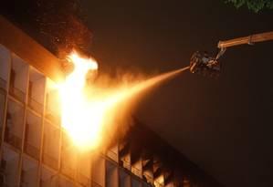 Bombeiros utilizam jatos de água para controlar o fogo Foto: Marcelo Carnaval / Agência O Globo