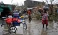 Moradores caminham por áreas inundadas após passagem do furacão Matthew em Les Cayes, no Haiti