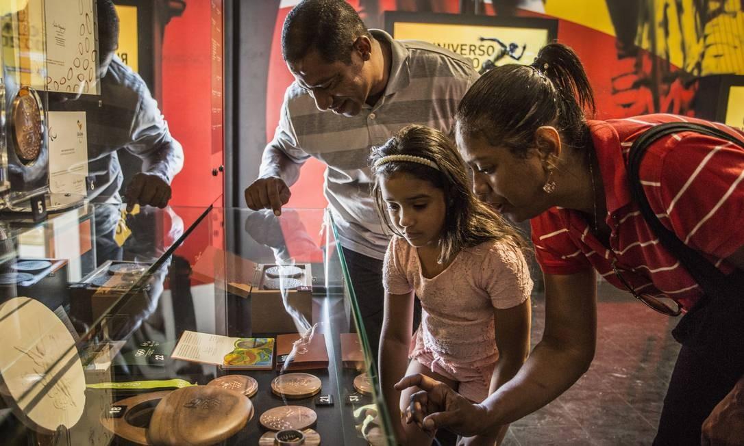 Família observa as medalhas dos Jogos Olímpicos e Paralímpicos Rio-2016, cunhadas pela Casa da Moeda e expostas no Museu Cidade Olímpica e Paralímpica, no Engenho de Dentro Foto: Ana Branco / Agência O Globo