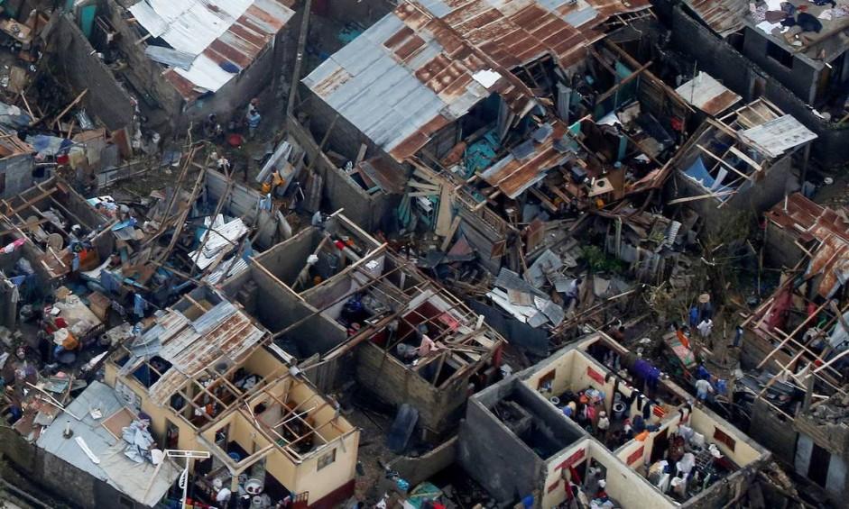 Pessoas recolhem pertences em casas destruídas após a passagem do furacão Matthew, em Jeremie, no Haiti Foto: CARLOS GARCIA RAWLINS / REUTERS