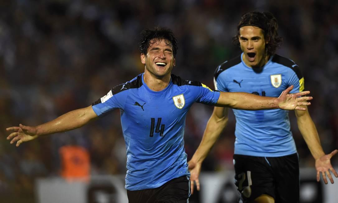 Em Montevidéu, Lodeiro abre os braços e comemora com Cavani o gol que abriu o placar para o Uruguai contra a Venezuela PABLO PORCIUNCULA / AFP