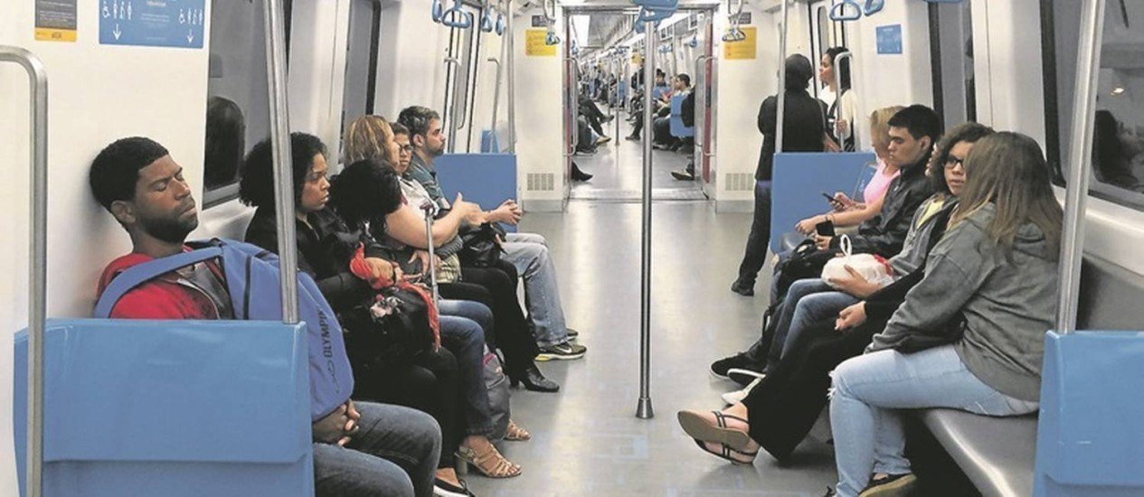 Por volta das 19h, em plena vigência do horário em que o espaço deveria ser apenas de passageiras, homens viajam no vagão exclusivo das mulheres num trem da Linha 2 Foto: Mônica Imbuzeiro
