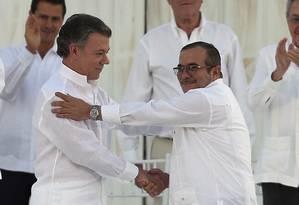 Presidente Juan Manuel Santos, à esquerda, e o líder das Farc, Rodrigo Londono, conhecido como Timochenko, se cumprimentam após assinarem acordo de paz no dia 26 de setembro Foto: Fernando Vergara / AP