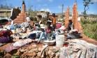 Uma mulher lava suas roupas no meio de sua casa destruída pelo furacão Matthew, na pequena aldeia de Casanette, no Haiti Foto: HECTOR RETAMAL / AFP