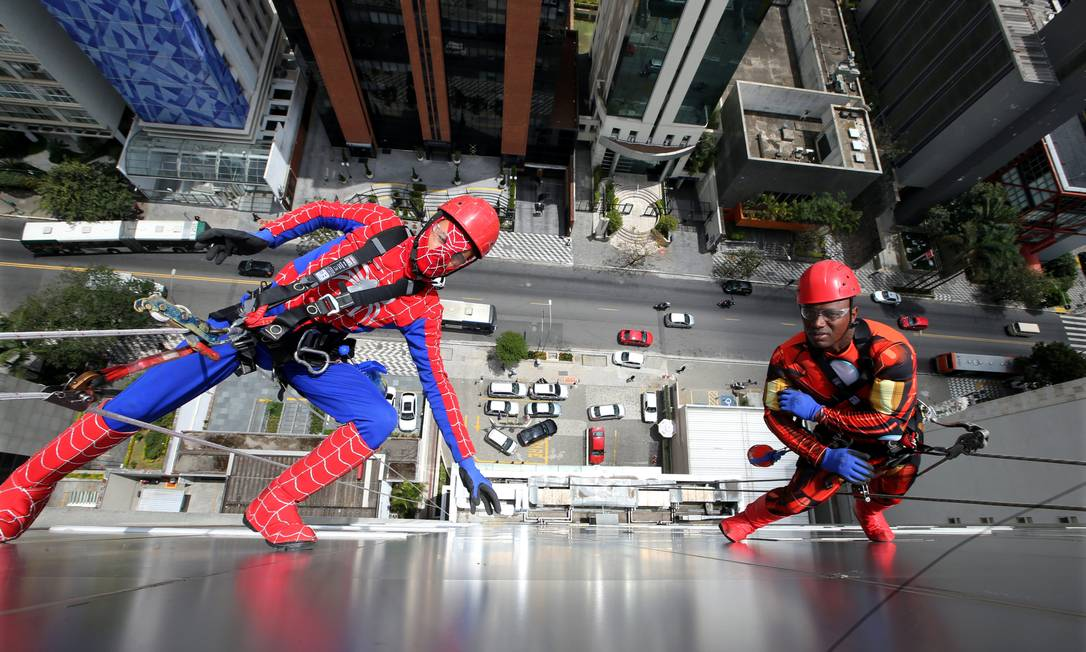 Homens, vestidos de Homem-Aranha e Homem de Ferro se preparam para limpar a fachada de vidro do Hospital Infantil Sabará, em São Paulo PAULO WHITAKER / REUTERS