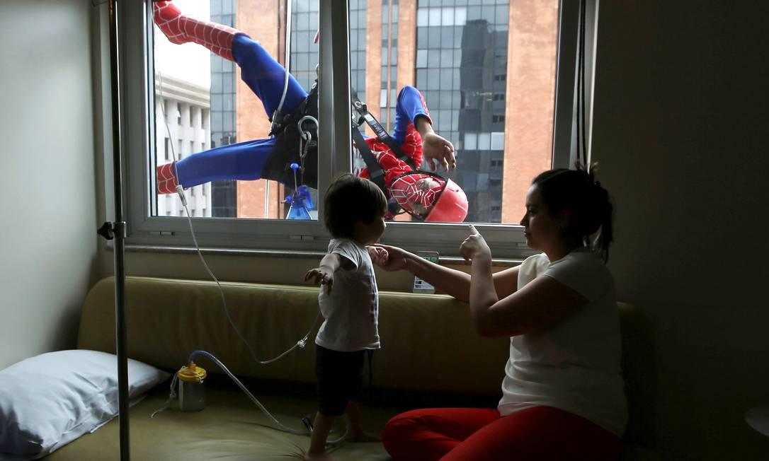 Durante a limpeza da fachada eles brincam com pacientes dos quartos. Na foto: Lucas e sua mãe PAULO WHITAKER / REUTERS