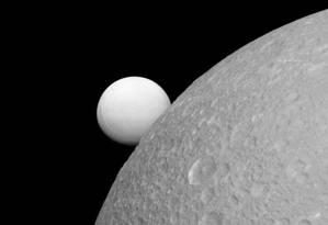 Dione, com Encélado ao fundo Foto: NASA
