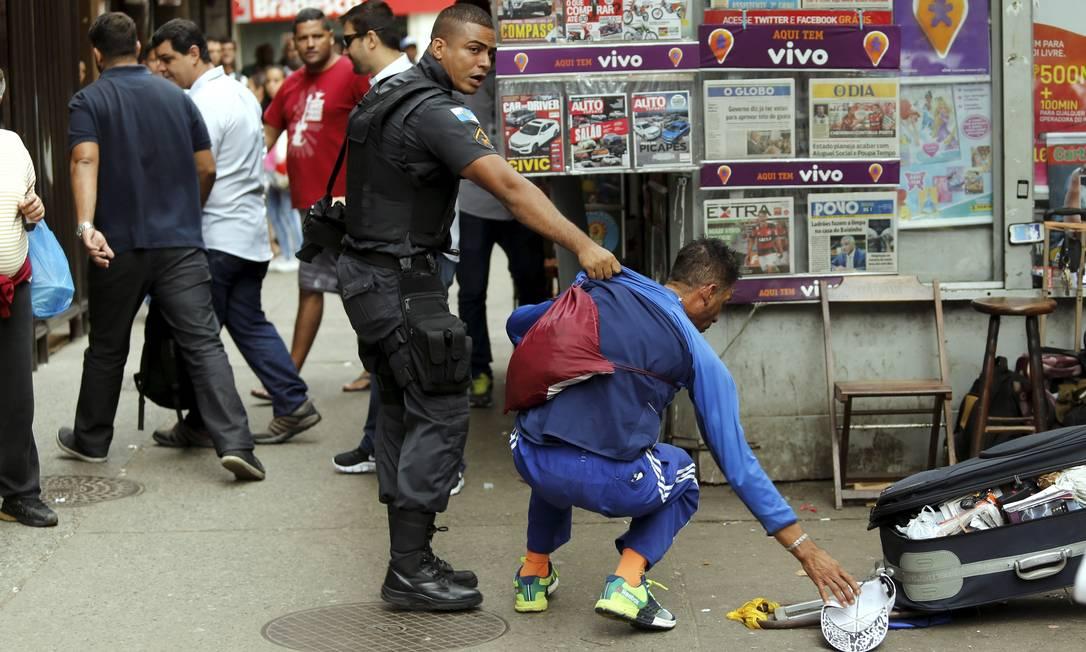 Policial discutie com morador Foto: Gabriel de Paiva / Agência O Globo