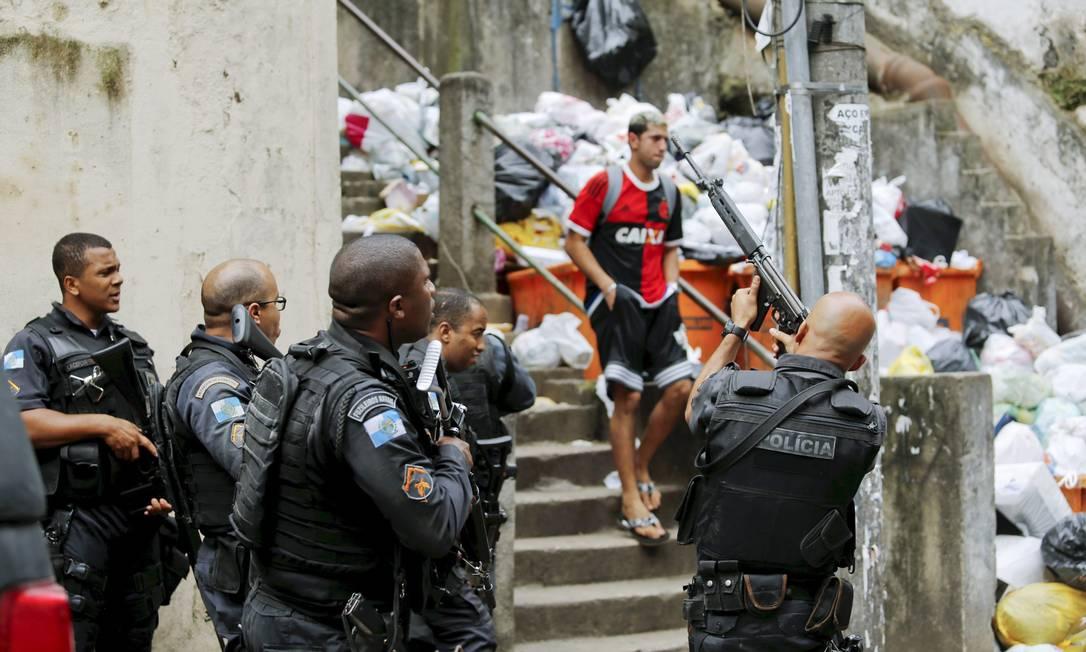 Morador desce as escadas do morro sem se preocupar com a ação policial Foto: Gabriel de Paiva / Agência O Globo