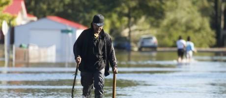 Pessoas caminham por ruas inundadas em Lumberton, na Carolina do Norte Foto: CARLO ALLEGRI / REUTERS