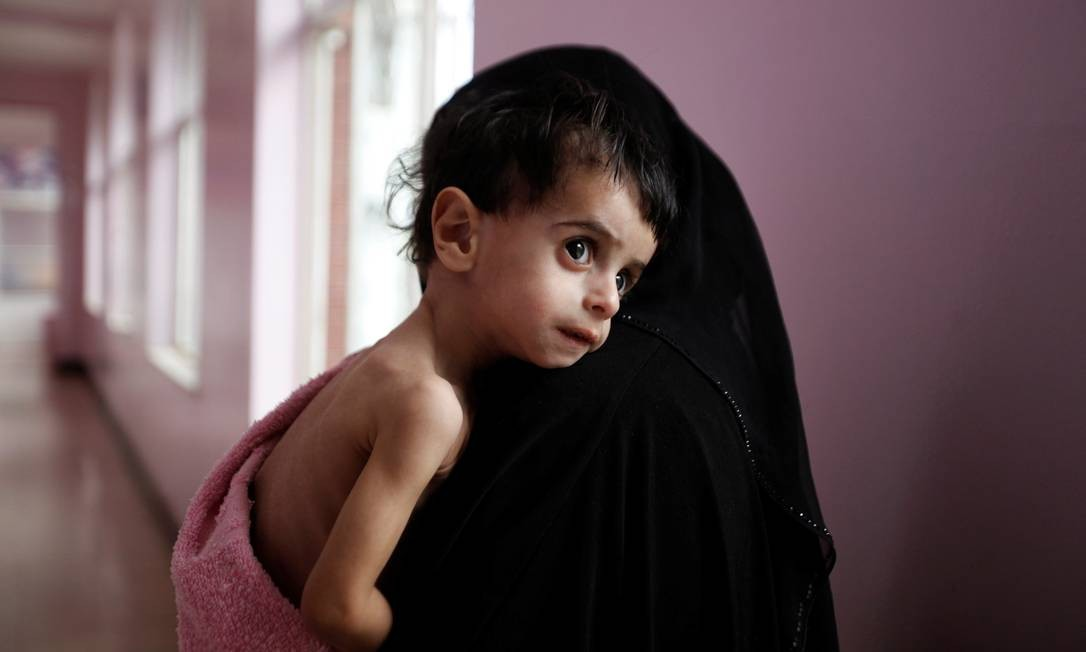 Uma mulher carrega seu filho, internado por desnutrição em um hospital em Sanaa, no Iêmen. Em guerra civil, país sofre com escassez de alimentos Foto: KHALED ABDULLAH