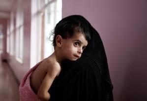 Uma mulher carrega seu filho, internado por desnutrição em um hospital em Sanaa, no Iêmen. Em guerra civil, país sofre com escassez de alimentos Foto: KHALED ABDULLAH / Agência O Globo