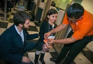Funcionário da Gol coloca a pulseira rasteadora em uma pequena passageira Foto: Gol / Divulgação