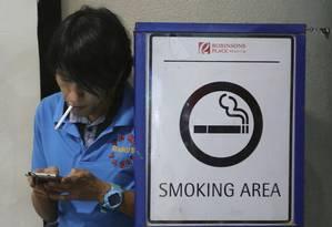 Um filipino fuma na área externa de um shopping em Manila, capital do país. Foto: Aaron Favila / AP