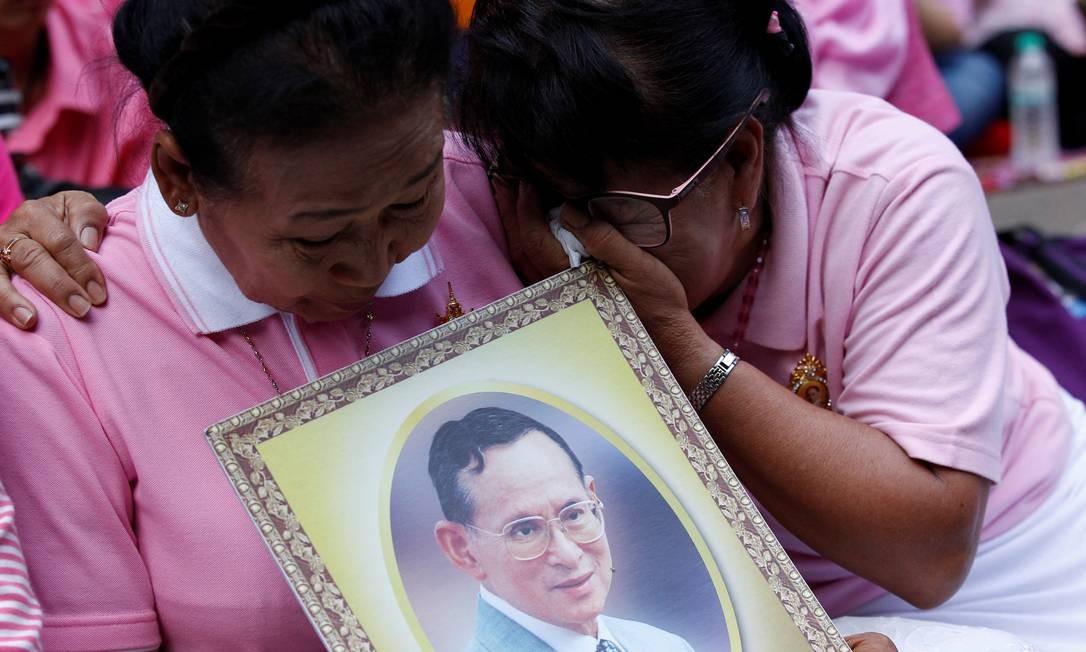 Mulheres rezam na porta do hospital Siriraj, em Bangcoc. Com lágrimas nos olhos, recordam o monarca morto na foto que carregam Foto: CHAIWAT SUBPRASOM / REUTERS