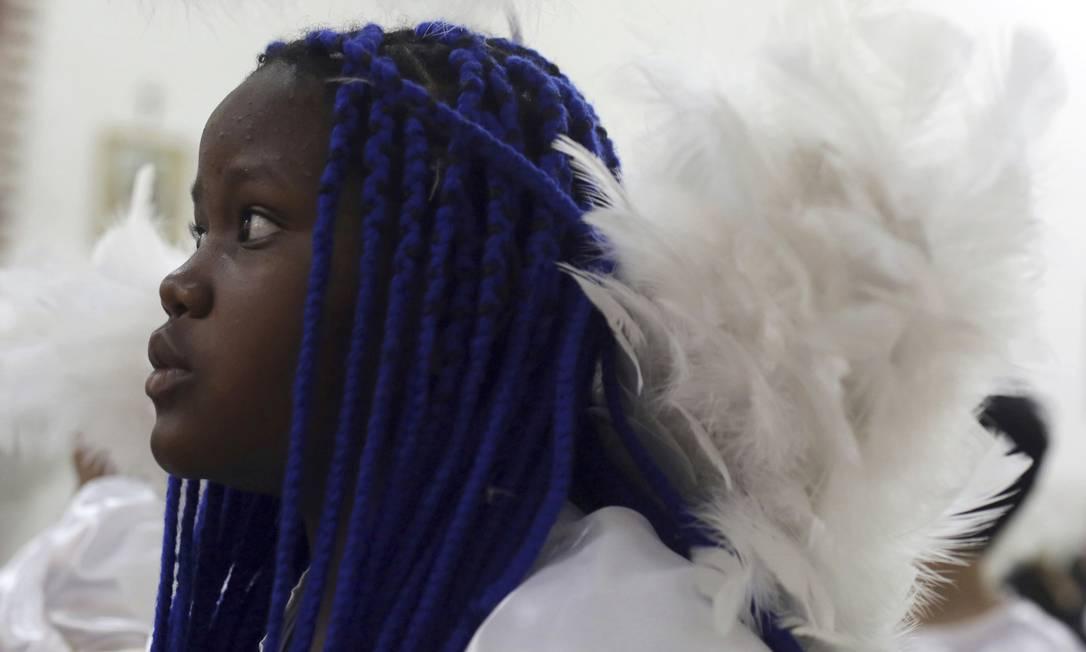 Menina vestida de anjo assiste a uma missa em honra de Nossa Senhora do Rosário Eraldo Peres / AP