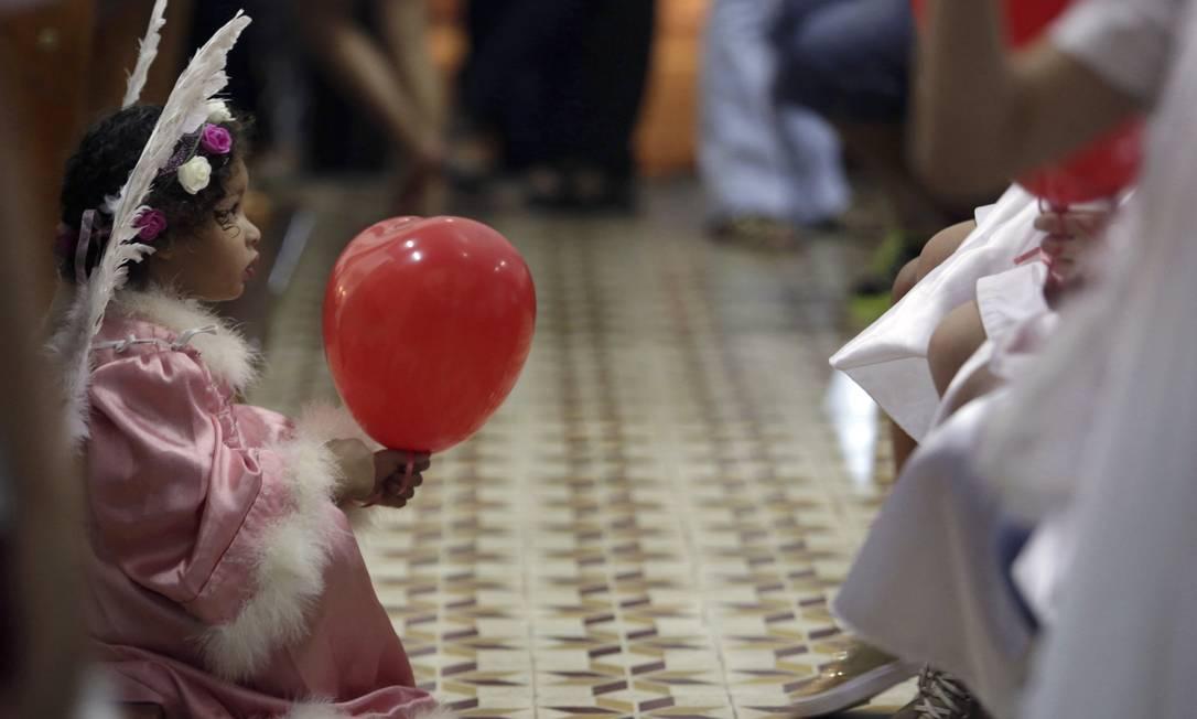 Algumas crianças participam da celebração vestidas de anjos, que é considerado um símbolo sagrado que representa a pureza Eraldo Peres / AP