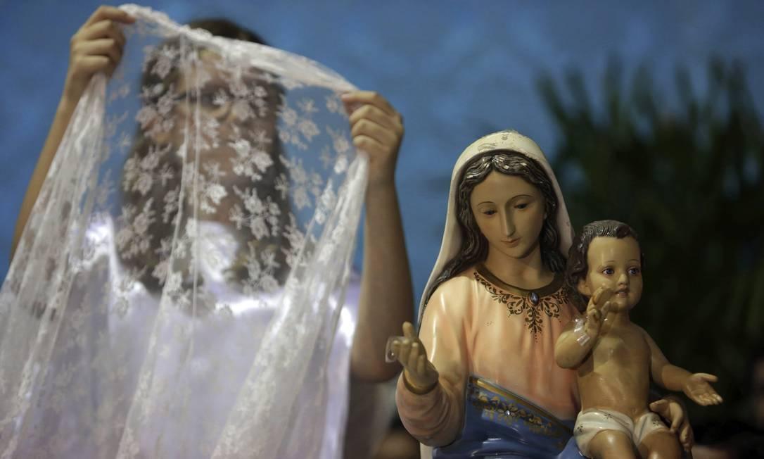 Uma jovem se prepara para colocar um véu sobre a estátua de Nossa Senhora do Rosário Eraldo Peres / AP
