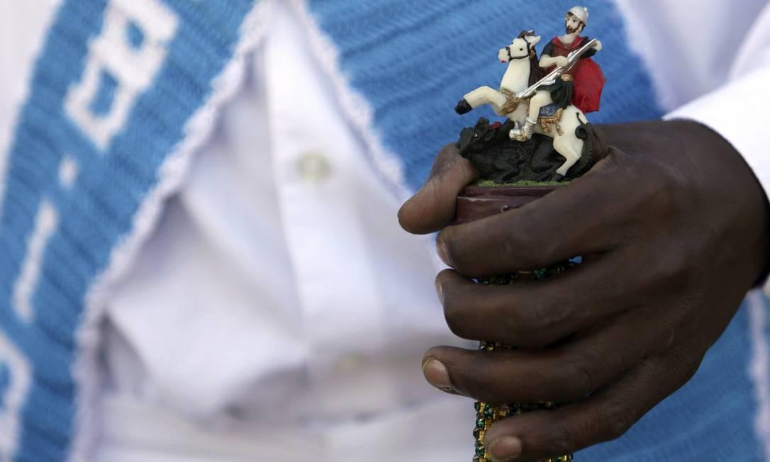 Homem segura uma bengala com a imagem de São Jorge durante uma tradição de dança afro-cristã Eraldo Peres / AP