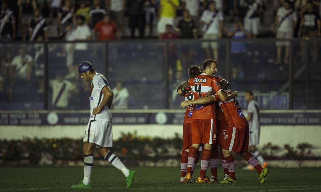 De touca na cabeça, o atacante Júnior Dutra passa desanimado, enquanto jogadores do CRB comemoram em São Januário a vitória sobre o Vasco Daniel Marenco / Agência O Globo