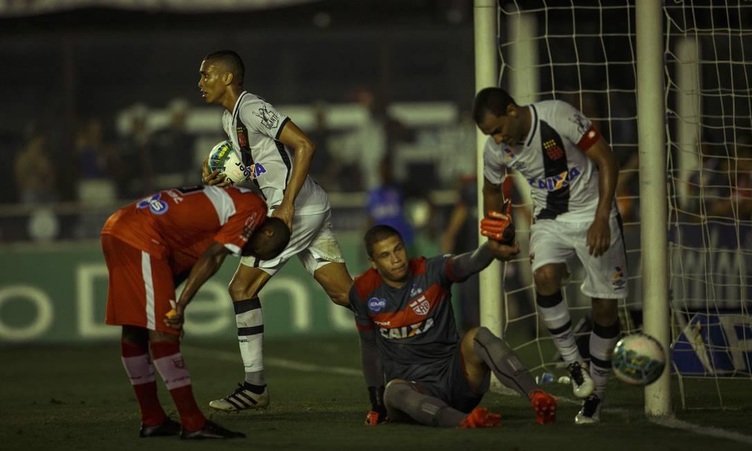 Enquanto Rodrigo ajuda o goleiro do CRB a se levantar, Madson leva a bola, com pressa, para o meio de campo: gol do Vasco saiu tarde demais no jogo Daniel Marenco / Agência O Globo